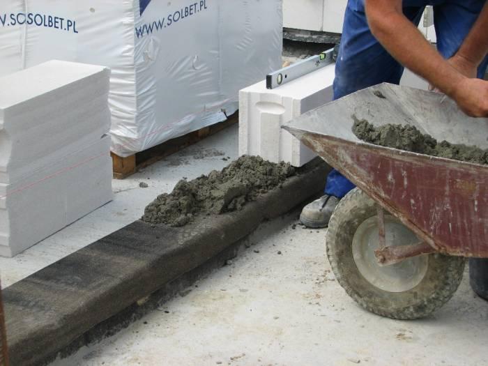 Legen der ersten Steinschicht aus Gasbeton auf der Wassersperre